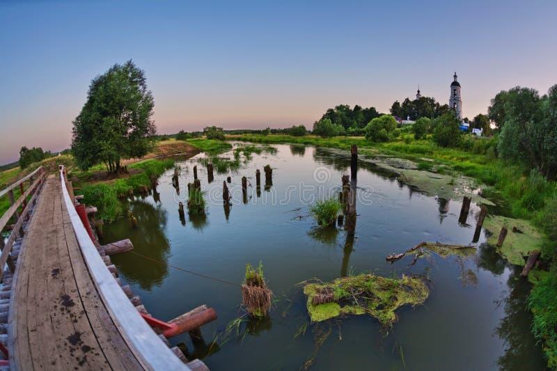 Ponte sobre um rio pantanoso no tempo do por do sol imagens de stock