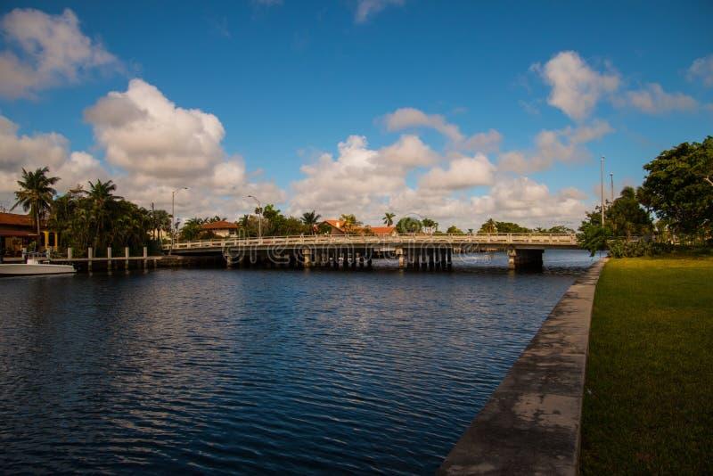 Ponte sopra il canale navigabile con cielo blu e le nuvole bianche gonfie fotografia stock