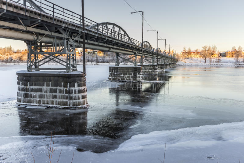 Ponte sopra il fiume congelato in Umeå, Svezia immagine stock