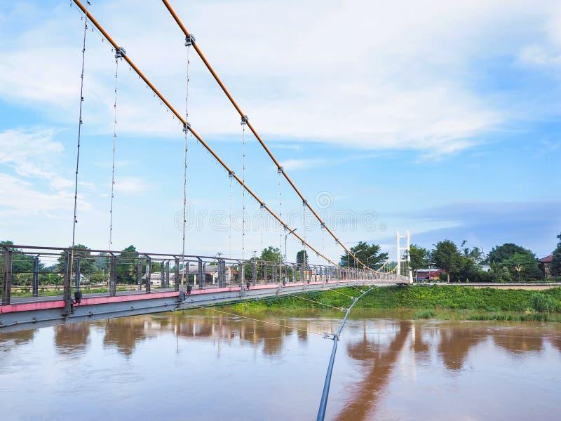 Ponte sospeso attraverso il fiume ed il cielo blu immagine stock libera da diritti