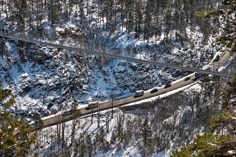 Ponte sospeso attraverso la strada principale alpina immagini stock libere da diritti