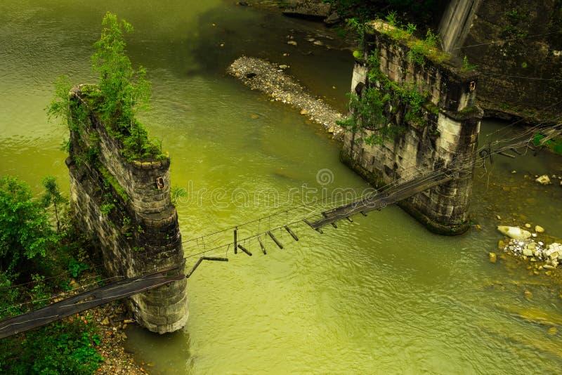Ponte sospeso pedonale rotto attraverso il fiume della montagna fotografie stock