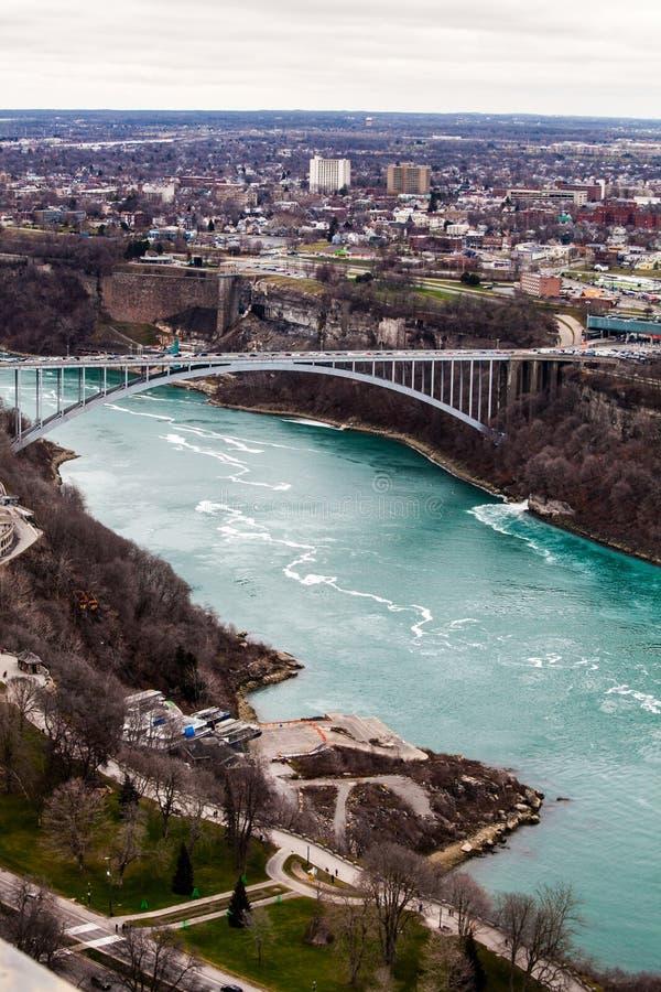 Ponte Stati Uniti e Canada, cascate del Niagara dell'arcobaleno del confine di frontiera Siluetta dell'uomo Cowering di affari immagine stock