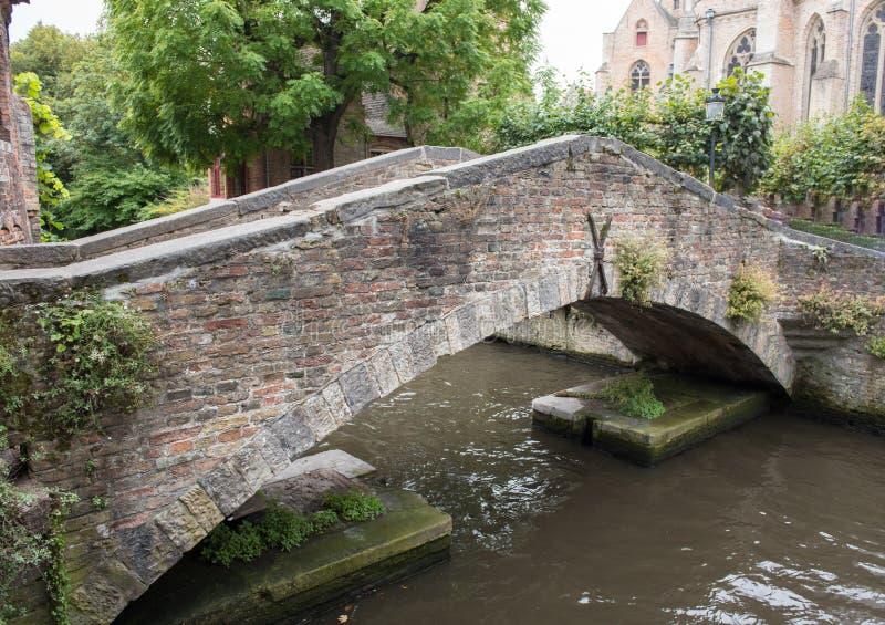 Ponte storico del mattone attraverso un canale a Bruges, Belgio immagini stock libere da diritti