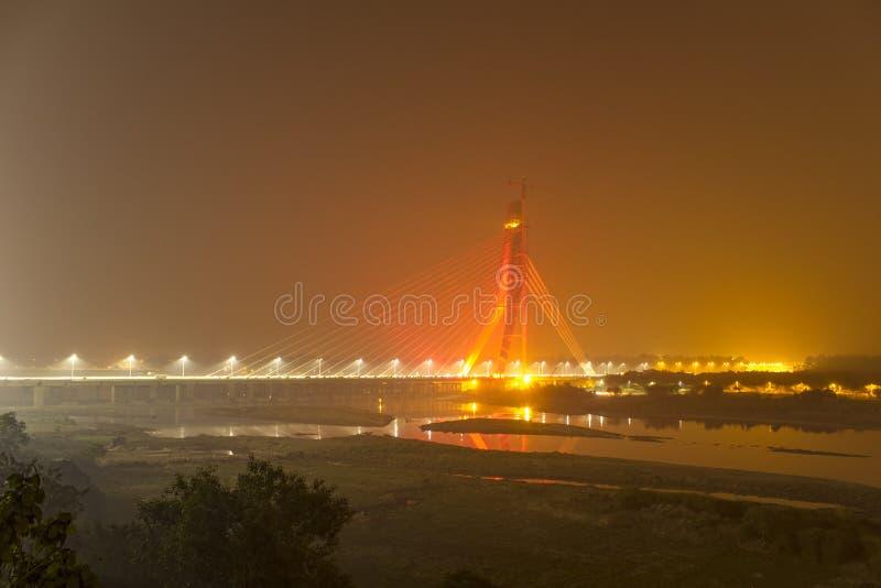 Ponte strallato illuminato attraverso il fiume di Yamuna alla notte Ponte della firma Delhi India immagini stock libere da diritti