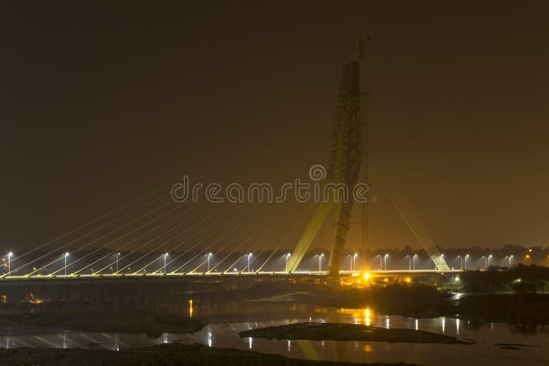 Ponte strallato illuminato in costruzione con una gru a torre sopra il fiume di Yamuna alla notte Ponte della firma delhi immagini stock libere da diritti