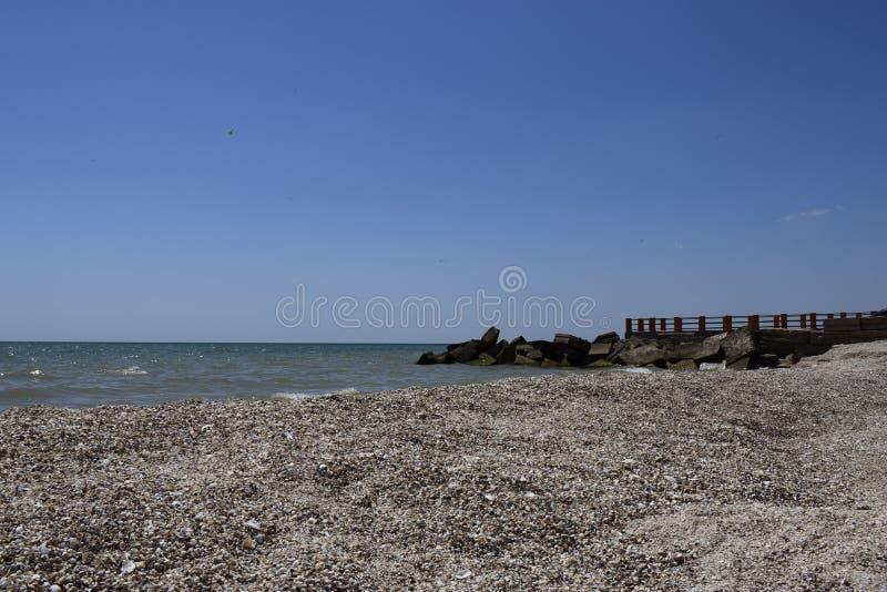 Ponte sul mare Rocce sull'acqua Glare sull'acqua di mare blu Sabbia e conchiglie sulla spiaggia immagini stock