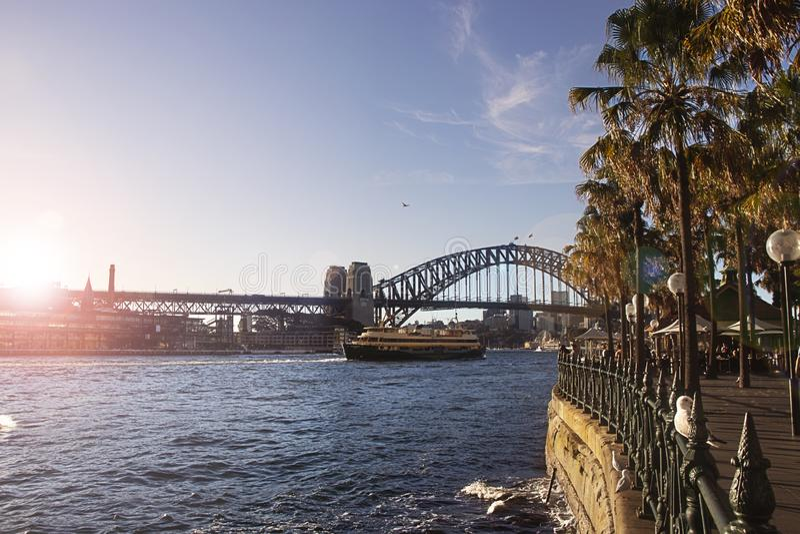 Ponte Sydney Harbor com sol dourado flare em mares calmos fotografia de stock royalty free