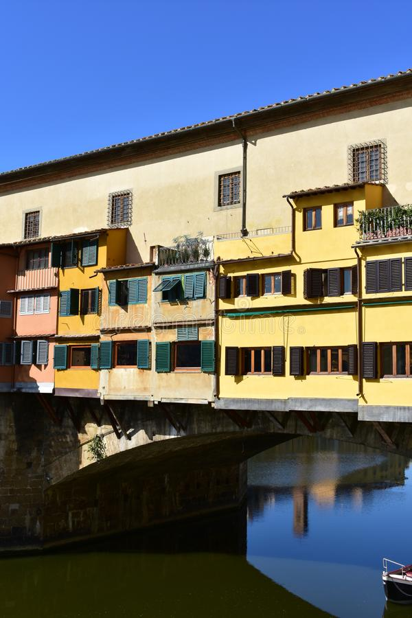 Ponte Vecchio and Arno River with blue sky. Colorful windows close-up. Florence, Italy. royalty free stock photo