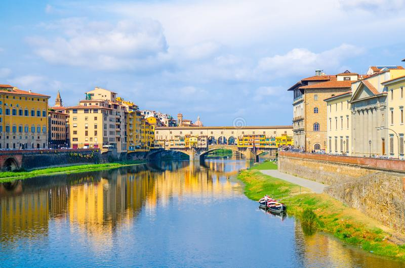 Ponte Vecchio bridge with colourful buildings houses over Arno River blue reflecting water and boats near river bank in Florence. Ponte Vecchio bridge with stock photos