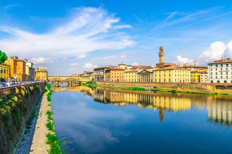 Ponte Vecchio bro med färgglade byggnadshus över Arno River blå reflekterande vatten och invallningpromenad i Florence royaltyfri bild