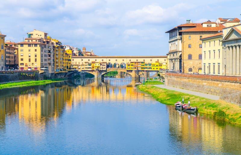 Ponte Vecchio bro med färgglade byggnadshus över Arno River blåa reflekterande vatten och fartyg nära flodbanken i Florence fotografering för bildbyråer