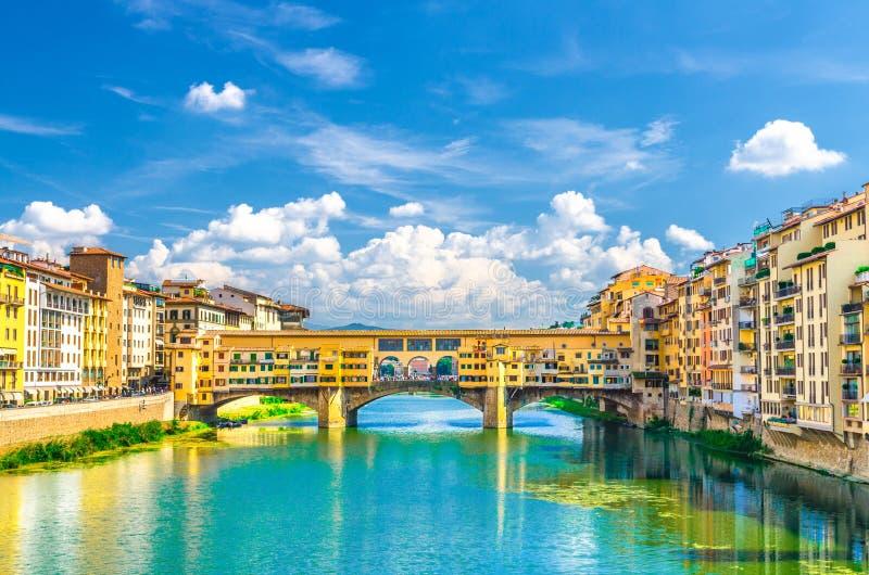 Ponte Vecchio stenbro med färgglade byggnadshus över Arno River blå turkosvatten och invallningpromenad i histor royaltyfri fotografi