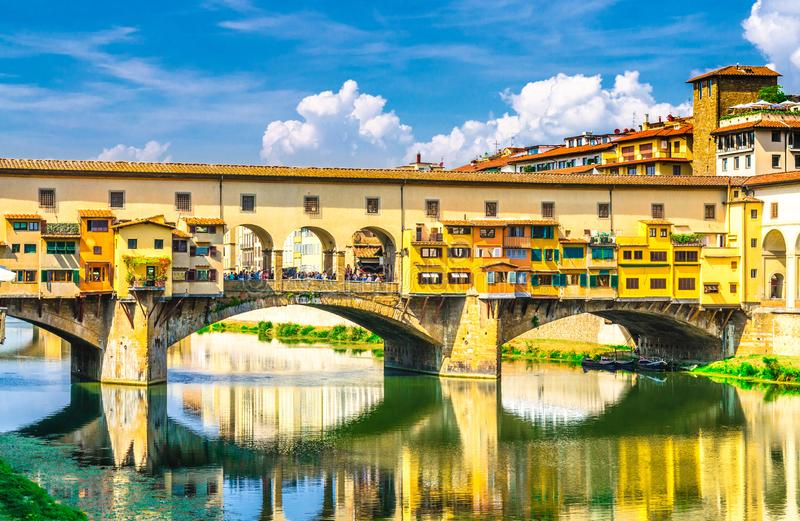 Ponte Vecchio stone bridge with colourful buildings houses over Arno River blue reflecting water in historical centre of Florence stock images