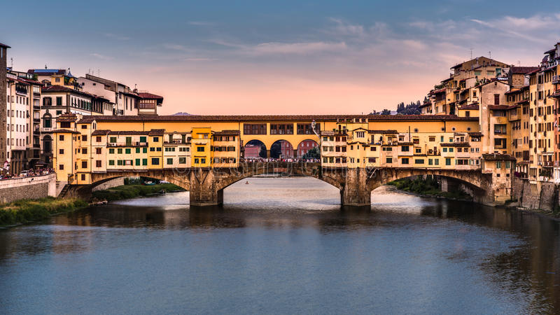 Ponte Vecchio before sunset. FLORENCE, ITALY - JULY 2013: Ponte Vecchio at sunset on July 24, 2013 in Florence, Italy. The bridge spans the Arno river at its stock images