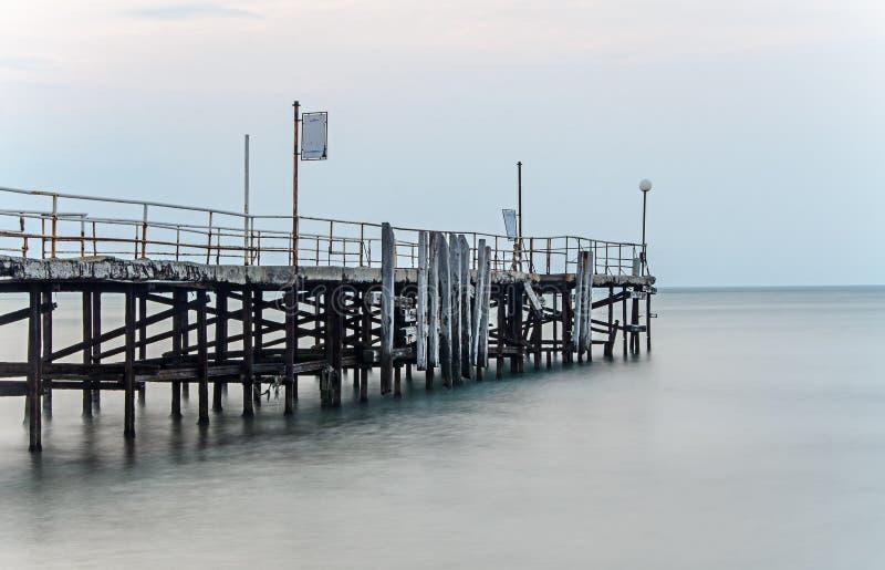 Ponte velha sobre a água do mar azul místico, a costa do Mar Negro foto de stock