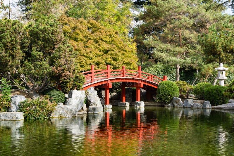 A ponte vermelha sobre um homem fez a lagoa, jardim japonês da amizade, área de San Jose, San Francisco Bay, Califórnia imagem de stock
