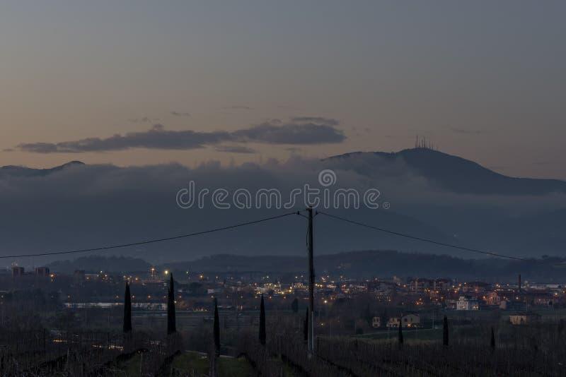 Pontedera e Monte Serra envolveram-se parcialmente no nevoeiro ao pôr do sol, Toscana, Itália foto de stock royalty free