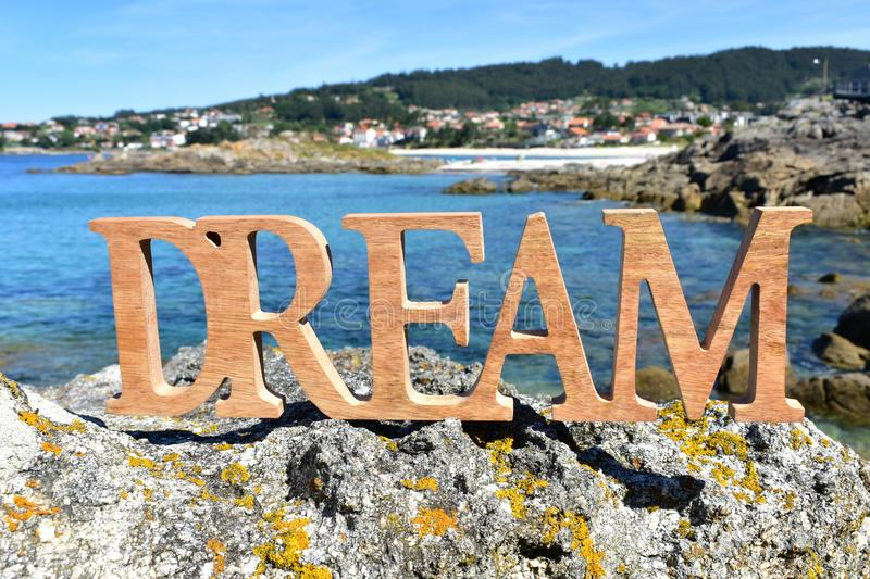 Coast and beach with Dream wooden sign on the rocks. Blue sea, sunny day. Rias Baixas, Spain. royalty free stock image
