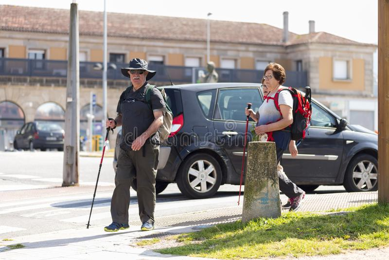 Some pilgrims walk down the street. PONTEVEDRA, SPAIN - MARCH 24, 2016: Some pilgrims walk down the street, making the way to Santiago royalty free stock photos