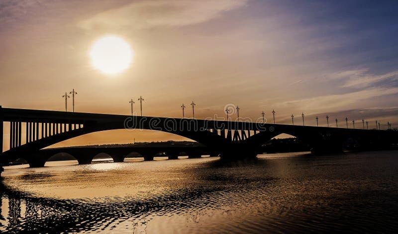 Ponti in siluetta sopra il fiume immagini stock