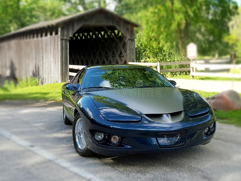 1999 Pontiac Firebird Classic Vintage Car in Front of a Covered Bridge stock photography
