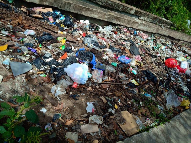 Pontianak, ИНДОНЕЗИЯ - 14-ое апреля 2019: Противозаконн-сброшенные отброс и полиэтиленовые пакеты загрязняют аграрный край 14-ого стоковые фотографии rf