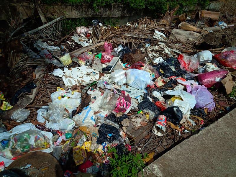Pontianak, INDONESIA - 14 aprile 2019: i sacchetti Illegale-scaricati di plastica e dell'immondizia contaminano il terreno agrico fotografie stock libere da diritti