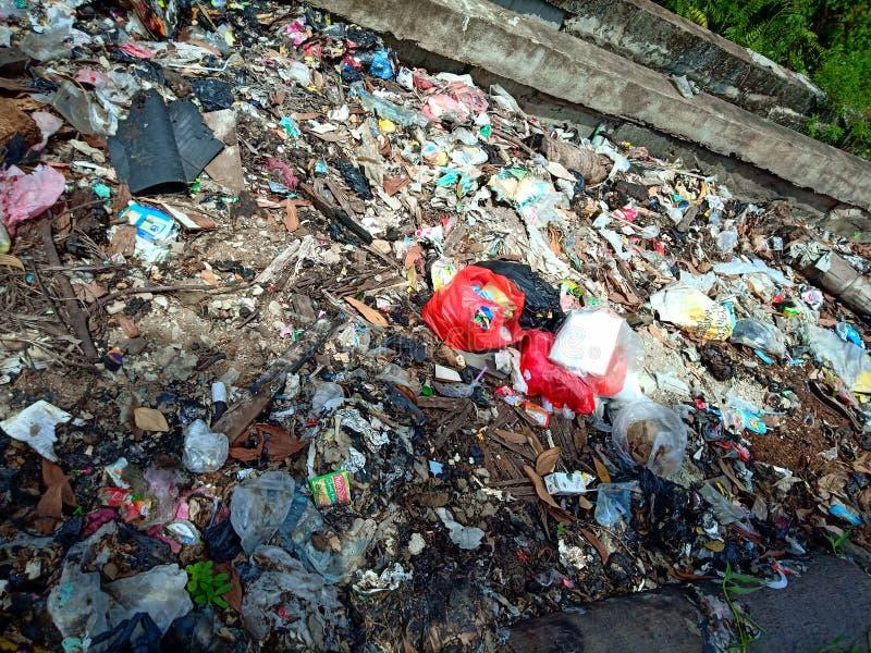 Pontianak, INDONESIA - 14 aprile 2019: i sacchetti Illegale-scaricati di plastica e dell'immondizia contaminano il terreno agrico fotografia stock libera da diritti