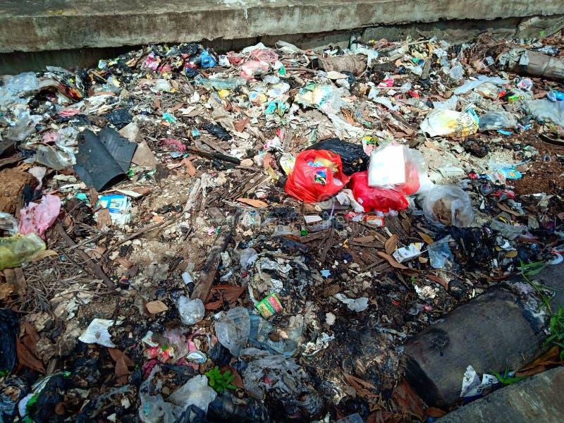 Pontianak INDONESIEN - April 14, 2019: Olaglig-dumpade avskräde och plastpåsar förorenar jordbruks- land på April 14, 2019 I fotografering för bildbyråer