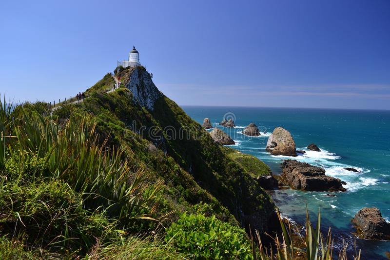 Ponto da pepita, paisagem romântica com farol branco, rochas originais no mar imagens de stock royalty free
