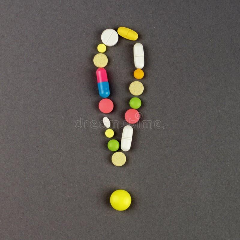 Ponto de exclamação criado dos comprimidos coloridos Conceito MÉDICO imagens de stock