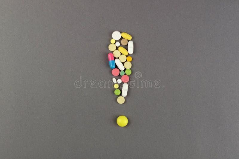 Ponto de exclamação criado dos comprimidos coloridos Conceito MÉDICO imagens de stock royalty free