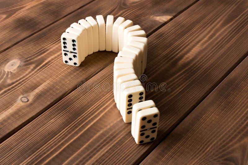 Ponto de interrogação do dominó na tabela de madeira Princípio do dominó fotos de stock royalty free