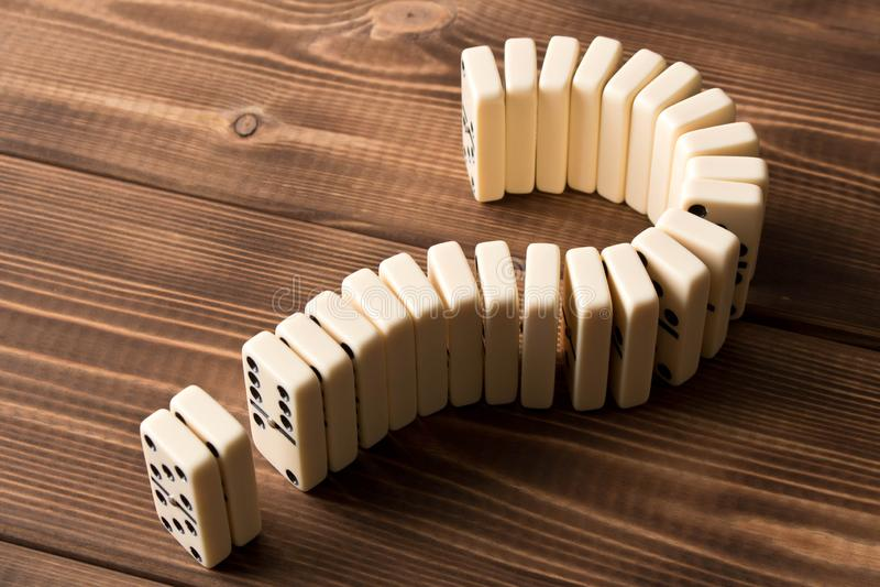 Ponto de interrogação do dominó na tabela de madeira Princípio do dominó fotografia de stock royalty free