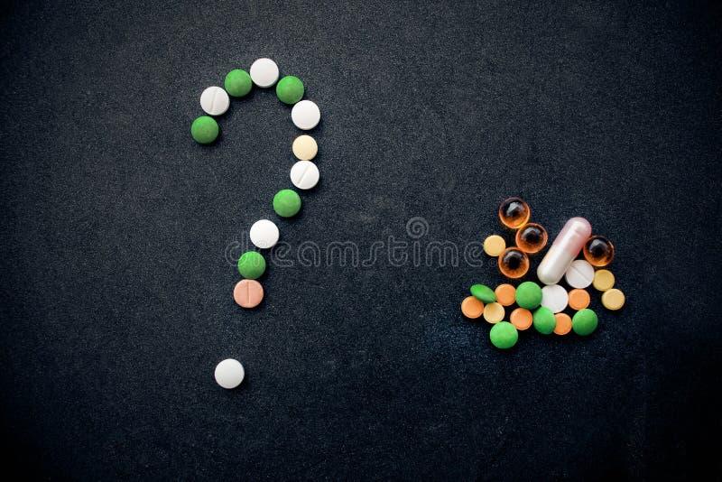 Ponto de interrogação do símbolo das tabuletas e das cápsulas coloridas no fundo preto fotografia de stock