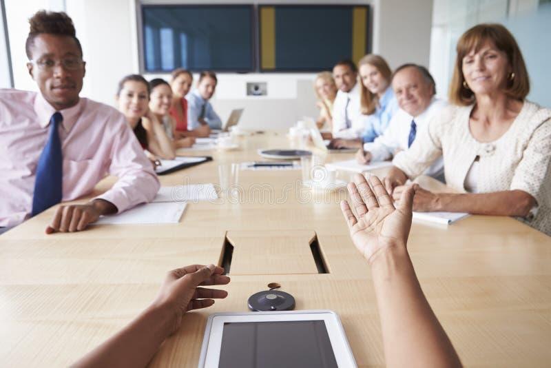 Ponto de vista disparado dos empresários em torno da tabela da sala de reuniões imagens de stock royalty free
