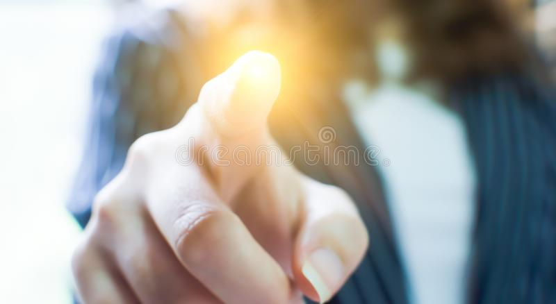 Ponto do dedo à luz com fundo do borrão da mulher de negócio imagem de stock royalty free