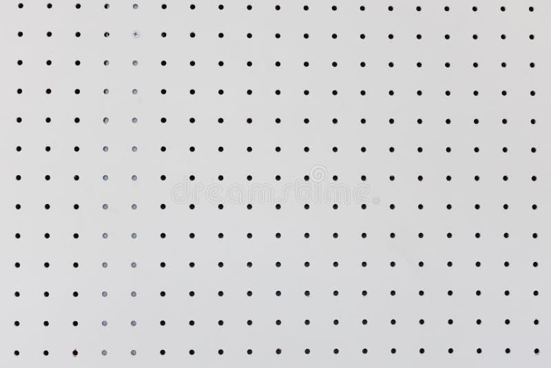 Ponto em ordem ou fileiras e colunas dos furos na parede branca do pegboard fotografia de stock royalty free