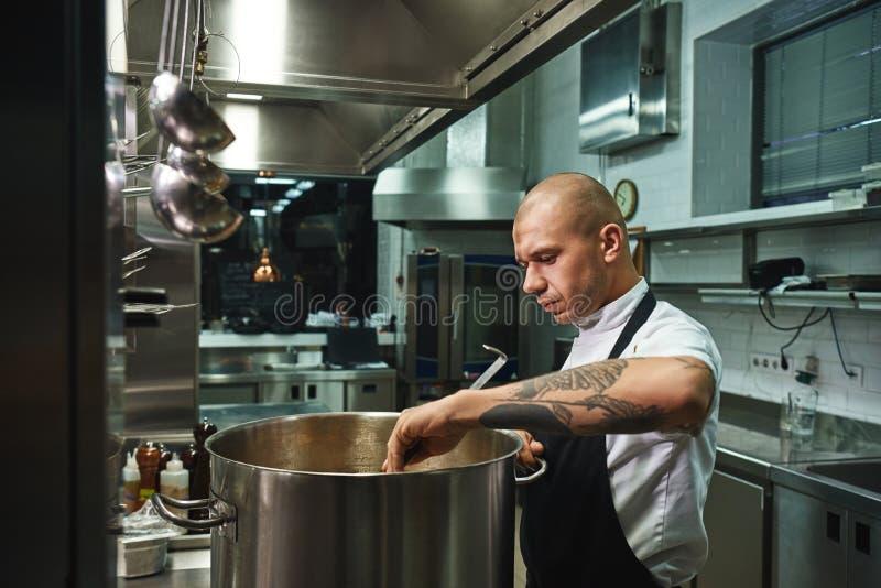 Ponto por ponto Cozinhando a sopa famosa pelo cozinheiro chefe masculino profissional em uma cozinha do restaurante fotografia de stock royalty free