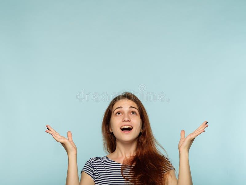 Ponto surpreendido alegre feliz do sorriso da menina acima acima da cabeça fotos de stock royalty free