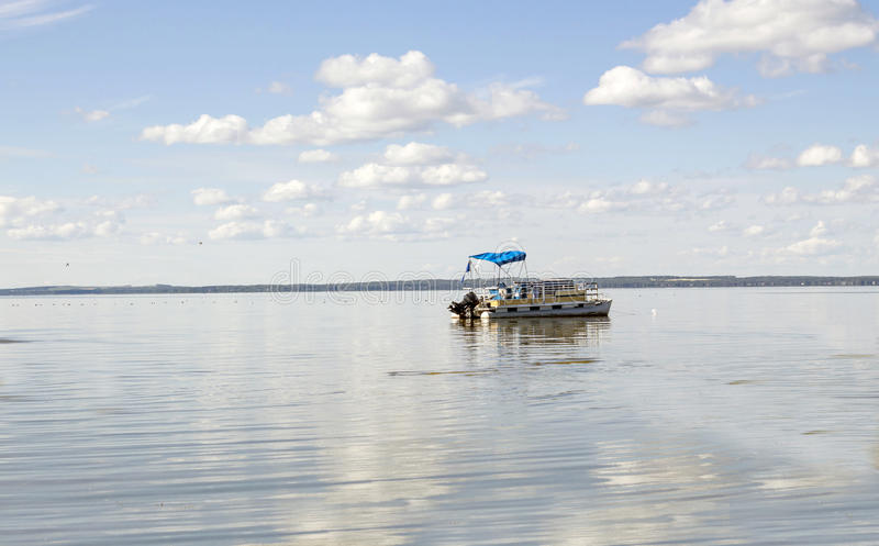 Pontoon boat coasting in a large body of water. royalty free stock photography