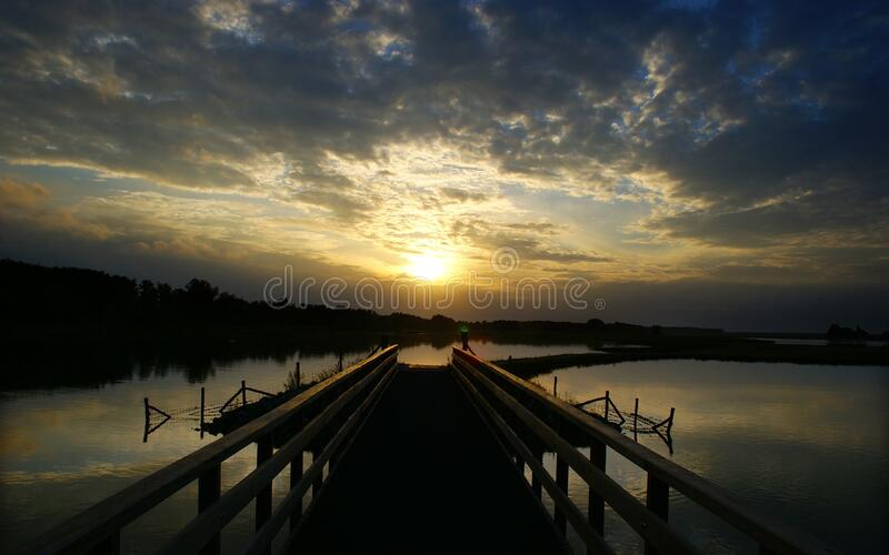 Pontoon over lake at sunset royalty free stock images