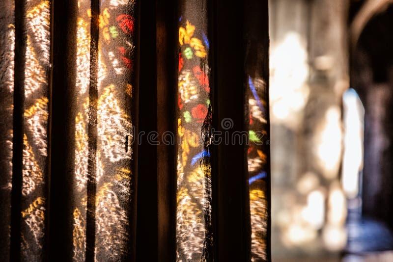 Pontos claros coloridos na parede na igreja Luz solar filtrada através da janela de vitral imagens de stock
