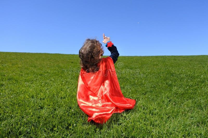 Pontos da criança do super-herói para o céu azul dramático fotografia de stock