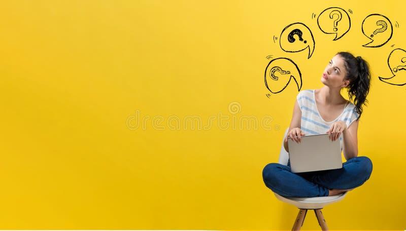 Pontos de interrogação com bolhas do discurso com a mulher que usa um portátil imagem de stock