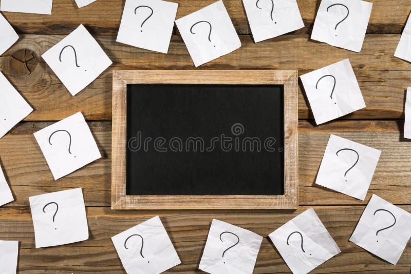 Pontos de interrogação em papéis de nota amarrotados em torno de um quadro pequeno imagem de stock royalty free