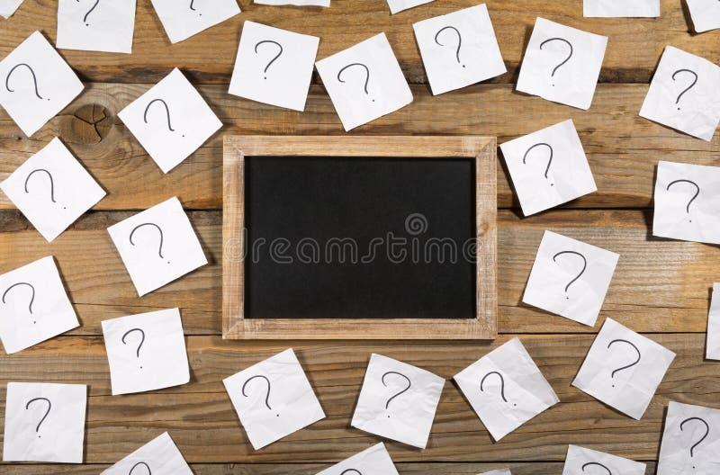 Pontos de interrogação no papel de nota amarrotado em torno de um quadro-negro vazio pequeno em um fundo de madeira fotografia de stock