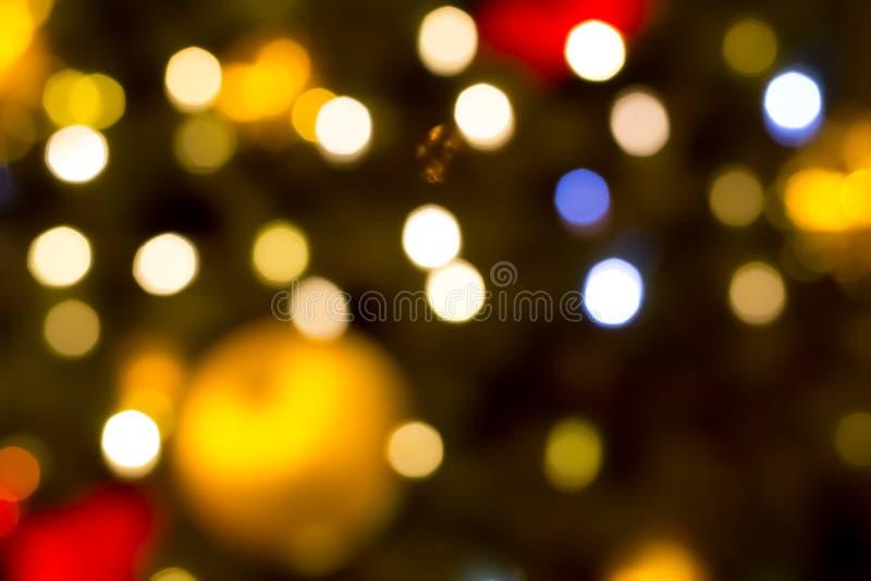 Pontos de luzes festivos coloridos no fundo de uma bola dourada dos azuis, a base de um Natal imagem de stock royalty free