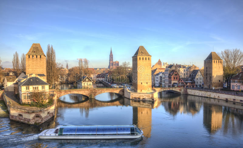 Ponts Couverts in Strasbourg, France. A touristic ship with tourists navigates in front of the famous Ponts Couverts in Strasbourg, France. In image there are royalty free stock photos